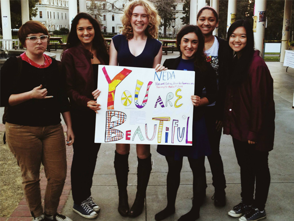 Some of the members of Body Positivity Club including Kendall Anderson (center) holding up a sign in honor of NEDA week. (Courtesy of Kendall Anderson)