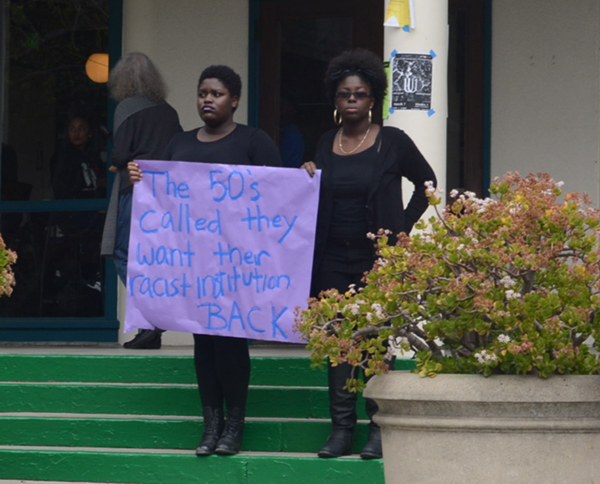 Black students staged a protest March 5th in response to the racist comment left on the now-defunct Mills College Confessions Facebook page as well as the culture of racism they feel is present at Mills at all times. Dressed in all black, the students held signs and stood silently for two hours on the Tea Shop steps. (Photo by Jen Mac Ramos)